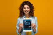 Fotografie smiling redhead woman holding digital tablet with booking app on screen while standing on orange