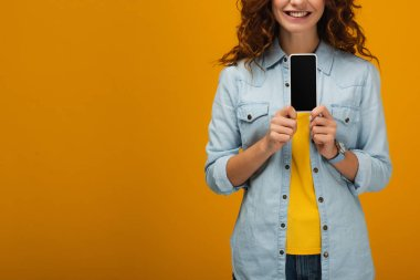 cropped view of cheerful curly woman holding smartphone with blank screen on orange