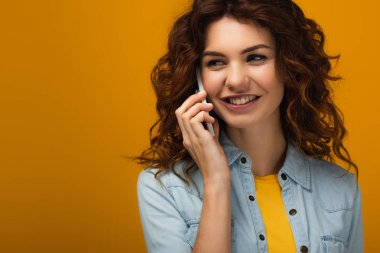 cheerful curly redhead woman talking on smartphone and smiling on orange