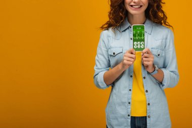 cropped view of cheerful curly woman holding smartphone with e-health app on screen on orange