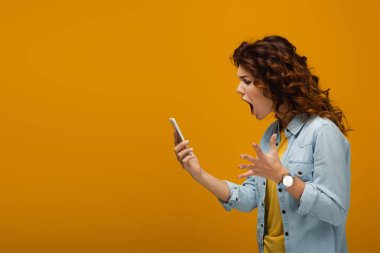 angry redhead woman gesturing while looking at smartphone and screaming on orange