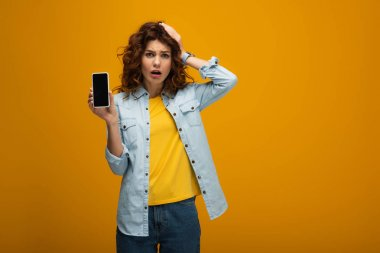 Surprised woman holding smartphone with blank screen and touching hair on orange stock vector