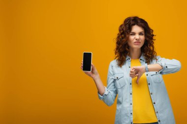 Redhead woman holding smartphone with blank screen and showing thumb down on orange stock vector
