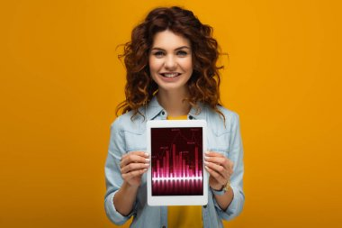 cheerful redhead woman holding digital tablet with charts and graphs on screen while standing on orange