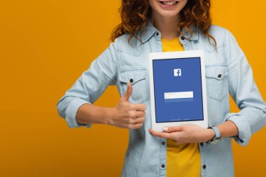 cropped view of cheerful curly girl holding digital tablet with facebook app on screen and showing thumb up isolated on orange