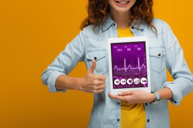 Cropped view of cheerful curly girl holding digital tablet with e health app screen and showing thumb up isolated on orange stock vector