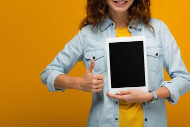 cropped view of cheerful curly woman holding digital tablet with blank screen and showing thumb up isolated on orange