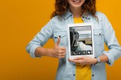 Fotografie cropped view of cheerful curly woman holding digital tablet with tickets app on screen and showing thumb up isolated on orange