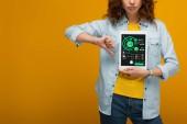 oříznutý pohled na smutnou složenou ženu držící digitální tablet s mapami a grafy na obrazovce, ukazující palec na oranžovou