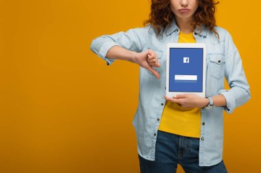 cropped view of upset curly woman holding digital tablet with facebook app on screen and showing thumb down on orange