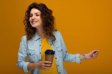 happy curly redhead girl holding coffee to go isolated on orange