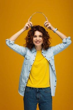 cheerful redhead girl smiling while holding headphones on orange