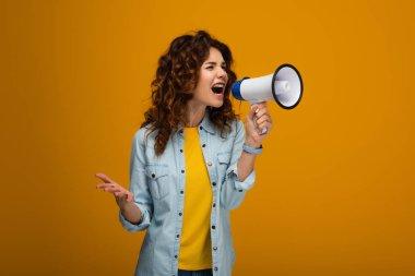 emotional curly redhead woman screaming in megaphone and gesturing on orange