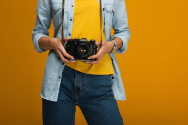 cropped view of young woman standing and holding digital camera on orange