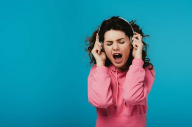 attractive curly woman singing while listening music in headphones on blue