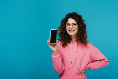 Cheerful curly girl in glasses standing with hand on hip and holding smartphone with blank screen on blue stock vector