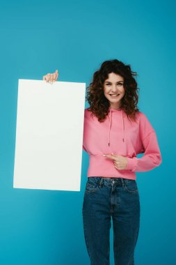 Happy curly redhead woman pointing with finger at blank placard on blue stock vector