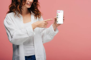 cropped view of cheerful girl pointing with finger at smartphone with apple music app screen on pink