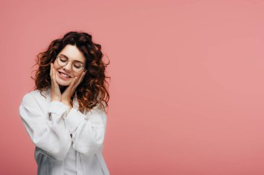 happy curly woman in glasses smiling while touching face on pink