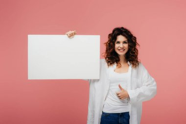 Happy curly woman with red hair holding blank placard and showing thumb up on pink stock vector
