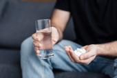 partial view of man holding glass of water and handful of drugs