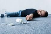 Bewusstloser Mann liegt auf grauem Boden in der Nähe von Wasserglas und Behälter mit Tabletten