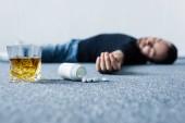 Bewusstloser Mann liegt auf grauem Boden neben Glas Whiskey und Behälter mit Pillen
