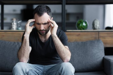 sad adult man holing hands near head while sitting on grey sofa at home