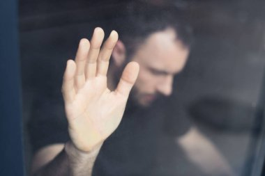 selective focus of frustrated man holding hand on window glass