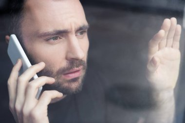 sad man with smartphone holding hand on window glass and looking away