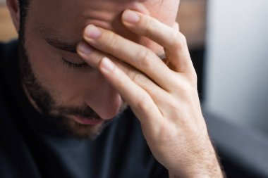 selective focus of upset man holding hand on forehead with closed eyes