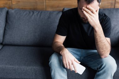 depressed man sitting on sofa with smartphone and holding hand on forehead