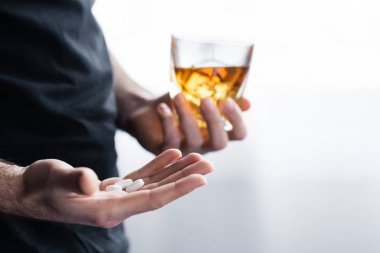 partial view of depressed man with glass of whiskey and handful of pills