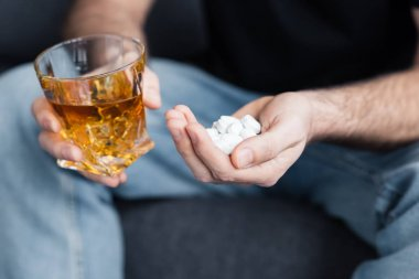 cropped view of sitting man with handful of pills and glass of whiskey