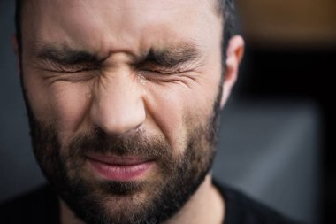 portrait of depressed bearded man crying with closed eyes