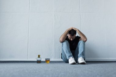 depressed man sitting on floor by white wall near bottle and glass of whiskey