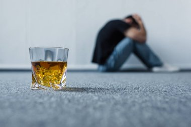 selective focus of depressed man suffering while sitting on grey floor near glass of whiskey