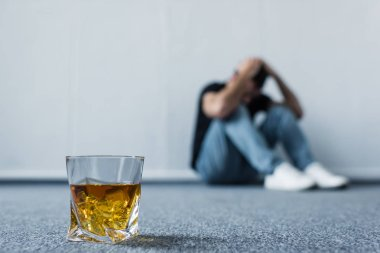 selective focus of depressed man sitting on floor by white wall near glass of whiskey