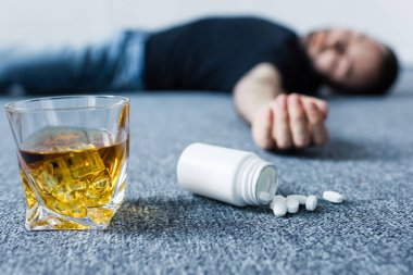 selective focus of unconscious man lying on floor near glass of whiskey and container with pills