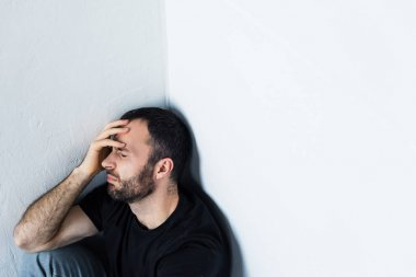depressed man sitting in corner with closed eyes and holding hand on forehead