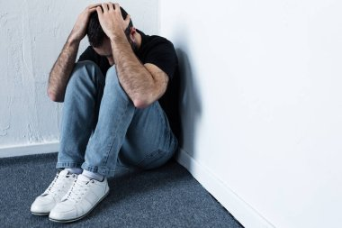 depressed man in blue jeans and white sneakers sitting in corner and holding hands on head