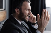irritated businessman screaming while talking on smartphone in office