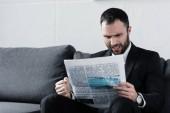 pěkný podrážděný podnik sedící na pohovce a čtení novin