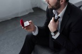 high angle view of sitting man in suite holding red gift box with ring