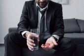 Ausgeschnittene Ansicht eines Mannes im schwarzen Anzug mit einem Glas Wasser und einer Handvoll Pillen