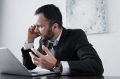 angry businessman quarreling while sitting at workplace and talking on smartphone