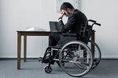 Fotografie depressed disabled businessman sitting in wheelchair at workplace with bowed head