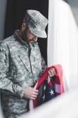 selektivní zaměření smutného vojenského muže v uniformě národní vlajky USA při stání u okna se skloněnou hlavou