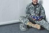smutný vousatý muž v vojenské uniformě, sedící na podlaze v rohu a držením národní vlajky USA