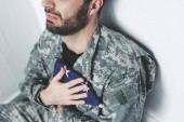 partial view of depressed military man sitting by white wall and holding usa military man near heart